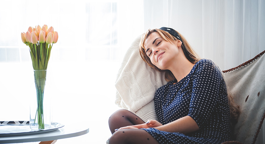 woman relaxing on chair in living room dreaming of the different strains of weed  to buy online in scarborough.