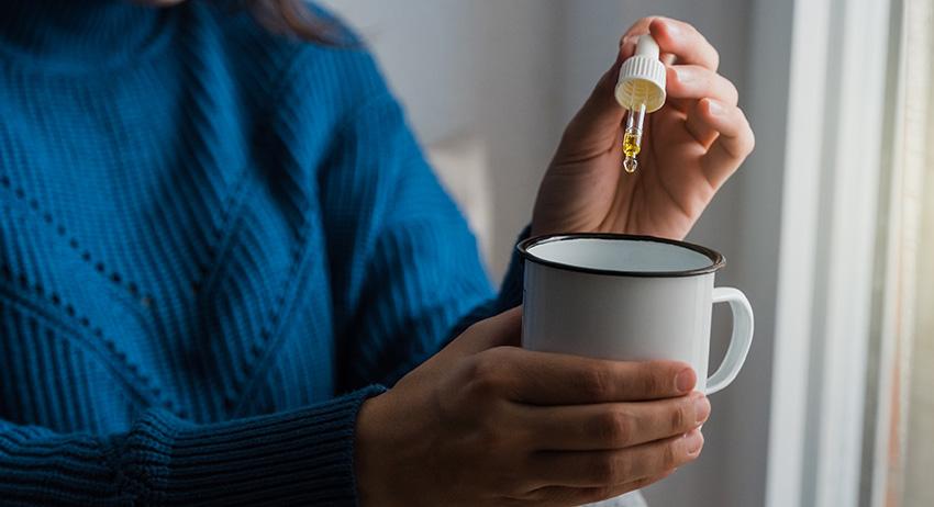 Woman taking CBD cbd oil inside tea cup. what is a good dose of cbd?