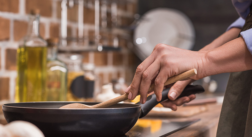 cropped image of woman stirring cannabis-infused vegetables on frying pan