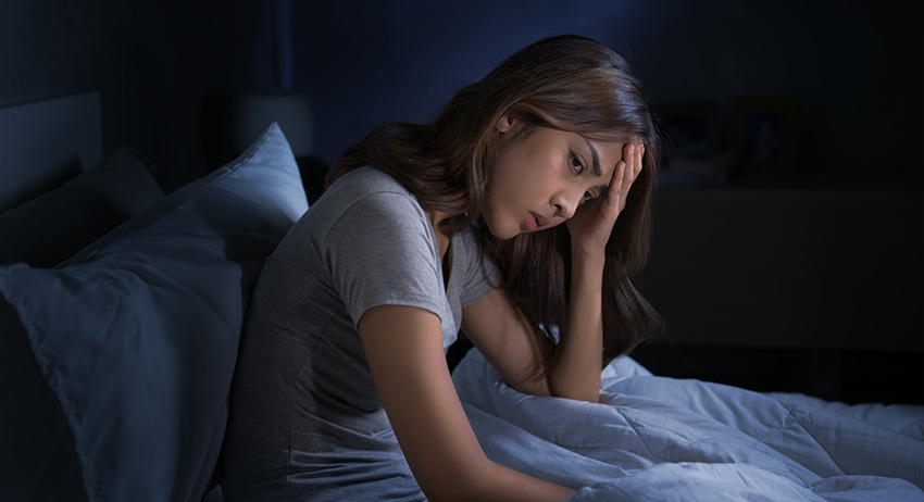 woman sitting in bed cannot sleep from insomnia. How much cbd oil to take for sleep?