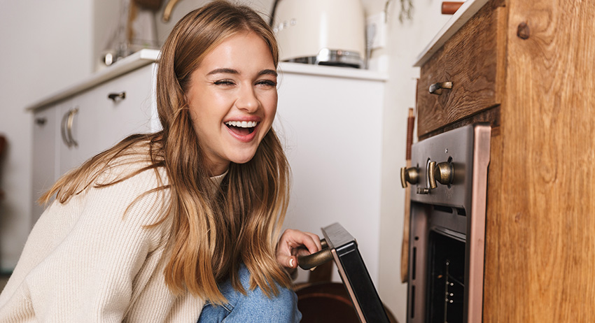 happy woman smiling in front of oven while cooking cannabis infused food at home.